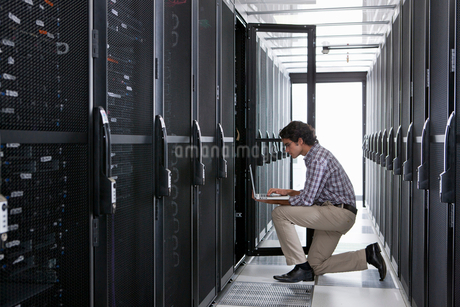 Technician, kneeling with laptop, checking aisle of server storage cabinets in data centerの写真素材 [FYI02112786]