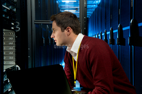 Technician checking server in storage cabinetの写真素材 [FYI02112820]