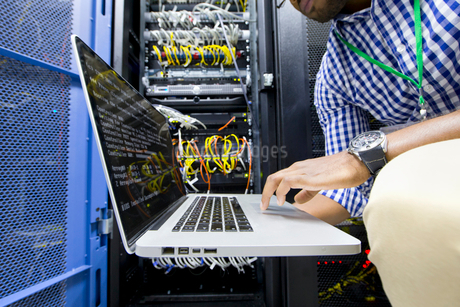 Technician with laptop checking server in data centreの写真素材 [FYI02112824]