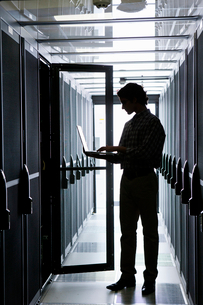 Technician with laptop, checking aisle of server storage cabinets in data centerの写真素材 [FYI02112870]