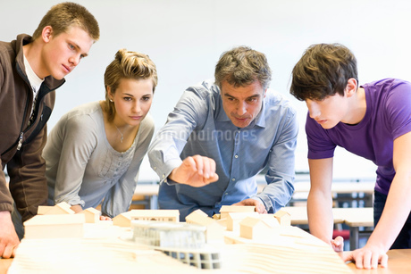 Mature man and teens gathered around an architectural modelの写真素材 [FYI02112874]