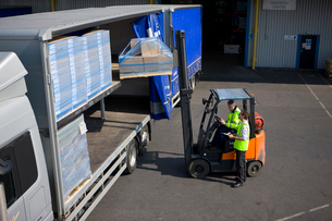 Worker driving forklift loading inventory on semi-truck on loading dockの写真素材 [FYI02112919]