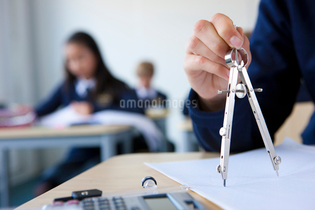 Student using drawing compass at desk in classroomの写真素材 [FYI02112948]