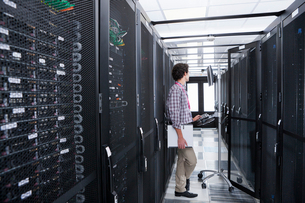 Technician working on computer in aisle of server storage cabinetsの写真素材 [FYI02112960]