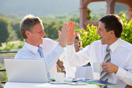 Happy businessmen giving high five and drinking coffee at cafナスの写真素材 [FYI02112984]