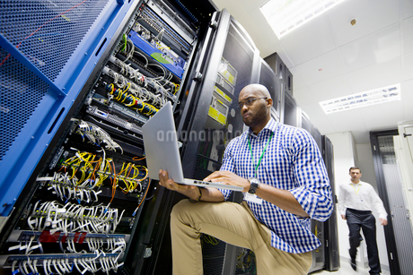Technician with laptop checking server in data centreの写真素材 [FYI02113000]