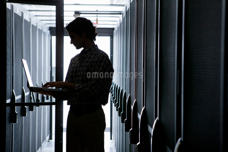 Technician with laptop, checking aisle of server storage cabinets in data centerの写真素材 [FYI02113045]