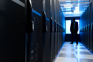 Manager standing in aisle of storage cabinets in data centerの写真素材 [FYI02113052]