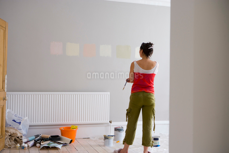 Woman looking at colour samples painted on wall, rear viewの写真素材 [FYI02113086]