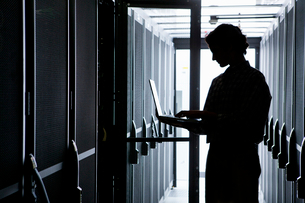 Technician with laptop, checking aisle of server storage cabinets in data centerの写真素材 [FYI02113159]