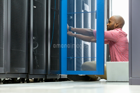 Technician with laptop checking server in data centreの写真素材 [FYI02113169]