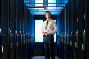 Manager standing in aisle of storage cabinets in data centerの写真素材 [FYI02113170]