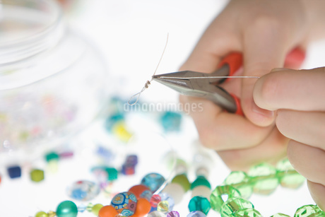 A young girl making a bead necklace with pliers and wire thread, close-up of handsの写真素材 [FYI02113187]