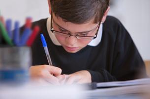 Close up of boy doing homeworkの写真素材 [FYI02113213]