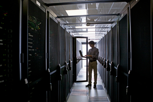 Technician with laptop, checking aisle of server storage cabinets in data centerの写真素材 [FYI02113245]