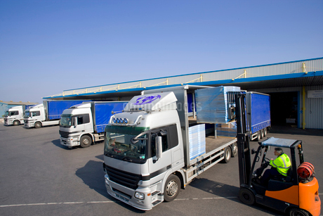 Worker driving forklift loading semi-truck on loading dockの写真素材 [FYI02113260]