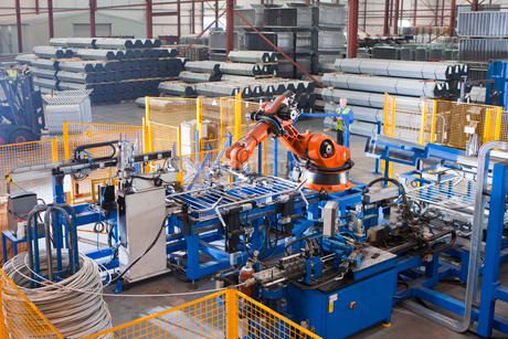Worker controlling robotic machinery lifting steel fencing on production line in manufacturing plantの写真素材 [FYI02113287]