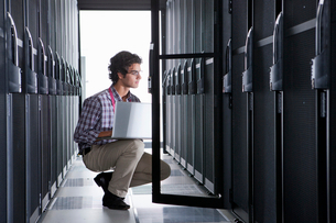 Technician, kneeling with laptop, checking aisle of server storage cabinets in data centerの写真素材 [FYI02113389]