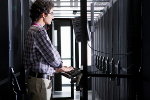 Technician working on computer in aisle of server storage cabinetsの写真素材 [FYI02113405]