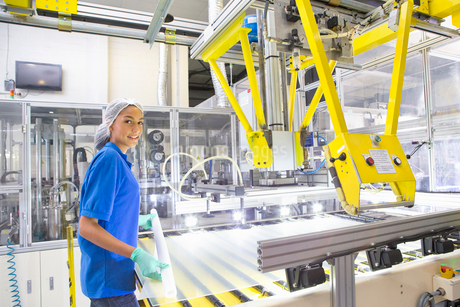 Factory floor worker smiling at camera and coating glass for solar panel assembly on production lineの写真素材 [FYI02113420]