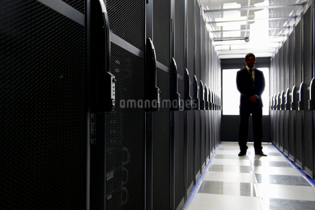 Manager standing in aisle of storage cabinets in data centerの写真素材 [FYI02113434]