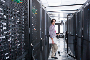 Technician, looking at camera, working on computer in aisle of server storage cabinetsの写真素材 [FYI02113443]