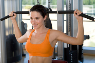 Woman using exercise equipment in gym, smiling, close-upの写真素材 [FYI02113449]