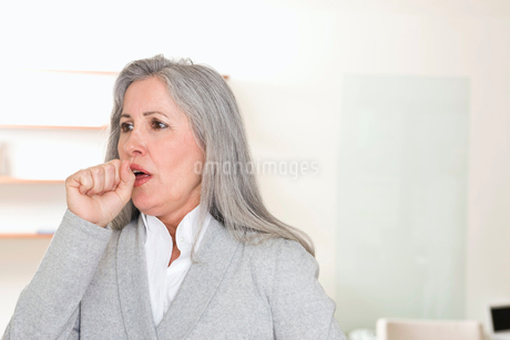 Mature woman coughingの写真素材 [FYI02113478]