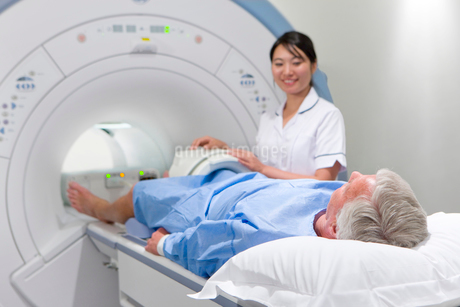 Radiologist helping patient with MRI scanning machineの写真素材 [FYI02113517]