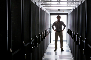 Technician standing in aisle of storage cabinets in data centerの写真素材 [FYI02113523]