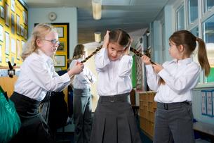 Mean, aggressive school girls teasing and pulling classmates braidsの写真素材 [FYI02113530]