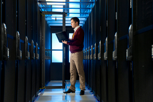 Technician with laptop, checking aisle of server storage cabinets in data centerの写真素材 [FYI02113567]