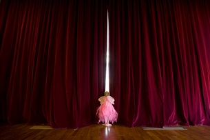 Ballerina girl (4-6) with fairy wings peeking out gap in stage curtains, rear viewの写真素材 [FYI02113573]