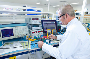 Engineer working at electrical test bench next to oscilloscopeの写真素材 [FYI02113639]