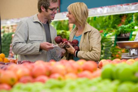 Couple choosing apples in grocery storeの写真素材 [FYI02113660]