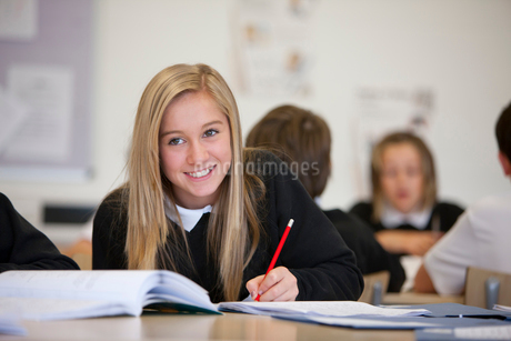 Smiling girl doing homework at desk in classroomの写真素材 [FYI02113768]