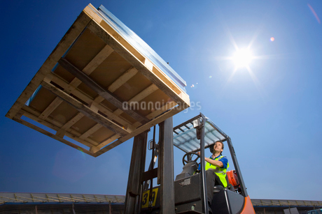 Worker moving merchandise on forkliftの写真素材 [FYI02113810]