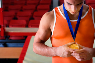 Male gymnast looking at gold medal around neck, close-upの写真素材 [FYI02113833]