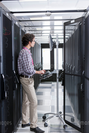 Technician working on computer in aisle of server storage cabinetsの写真素材 [FYI02113842]