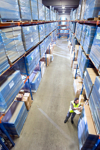 Warehouse worker with clipboard checking inventoryの写真素材 [FYI02113843]