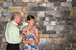 Mature man flirting with younger woman beside stone wall, holding glasses of white wine, woman lookiの写真素材 [FYI02113886]