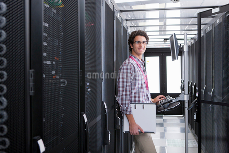 Technician, smiling at camera, working on computer in aisle of server storage cabinetsの写真素材 [FYI02113899]