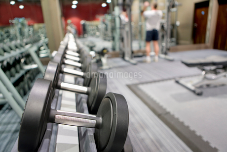 Rack of dumbbells in health club with man lifting weights in backgroundの写真素材 [FYI02114005]