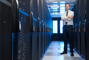 Manager standing in aisle of storage cabinets in data centerの写真素材 [FYI02114028]