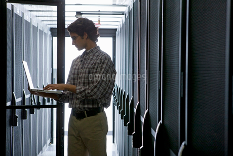 Technician with laptop, checking aisle of server storage cabinets in data centerの写真素材 [FYI02114030]