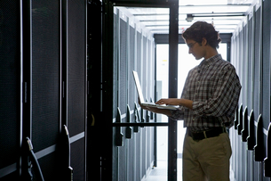 Technician with laptop, checking aisle of server storage cabinets in data centerの写真素材 [FYI02114047]