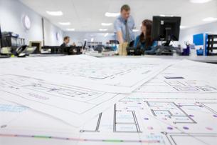 Engineers working at desk behind circuit diagrams in officeの写真素材 [FYI02114062]