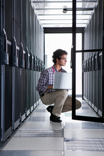 Technician, kneeling with laptop, checking aisle of server storage cabinets in data centerの写真素材 [FYI02114065]