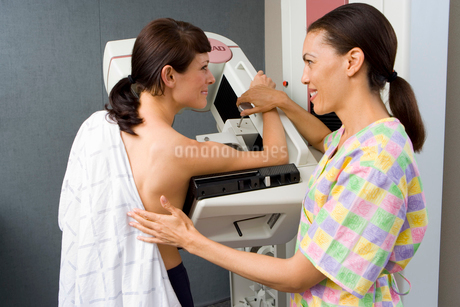 Consultant helping topless woman have mammogram, smilingの写真素材 [FYI02114066]