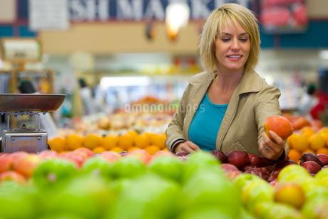 Woman choosing apples in grocery storeの写真素材 [FYI02114091]